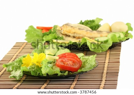 A plate with salad, on a background a dish with fried fish.