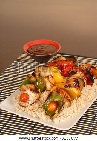 A platter of chicken kabobs on rice with honey BBQ sauce - stock photo