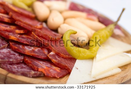 A platter of cold meats, cheese slices, green chili, and mini-baguettes served as an appetizer