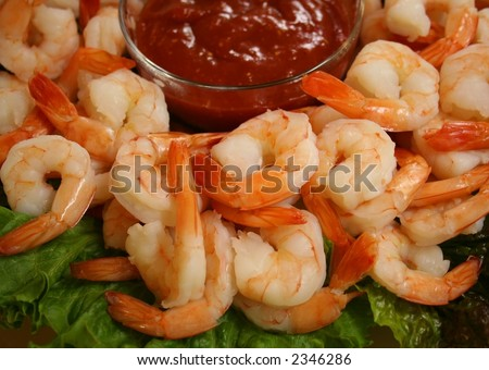A platter of cooked shrimp with a bowl of cocktail sauce. - stock photo