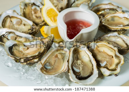 A platter of fresh organic raw oysters on ice at restaurant - stock photo