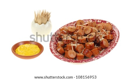 A platter of grilled sliced hot dog pieces with cheese.