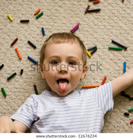 A playful boy sticks his tongue out as he lies on the floor, with crayons strewn all over.