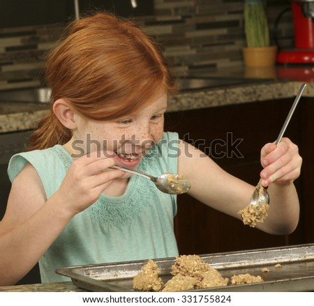 A playful female Caucasian girl  happily making cookies - stock photo