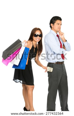 A playful smiling female shopper with store shopping bags secretly removing money unnoticed from her pushover husband pants pocket while he is looking away V - stock photo