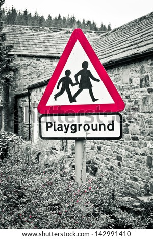 A playground warning sign with selective color desaturation - stock photo