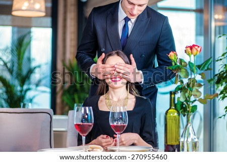 A pleasant surprise. Romantic dinner in the restaurant. Young couple sitting at a table in the restaurant until the guy closed her eyes with his hands - stock photo