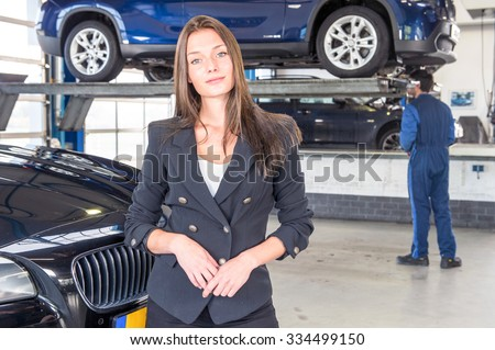 A pleased customer, posing in front of her justly fixed car at a high end garage, with a mechanic tending to another vehicle in the background - stock photo