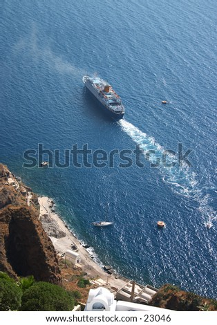 A pleasure cruise ship leaving the port of Fira on Santorini, Greece, seen from cliffs 1,000 feet above. - stock photo