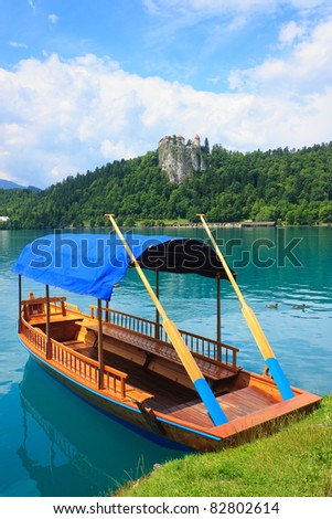 A pletna, traditional Slovenia boat, on Lake Bled with Bled Castle in the background - stock photo