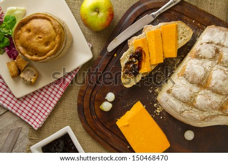 A ploughmans lunch fare, spread out on burlap, bread board and distressed boards. Melton Mowbray pork pie with artisan boule bread in basket, next to red Leicester cheese, butter, salad and an apple. - stock photo