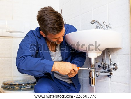 a plumber (insatallateur) at work - stock photo