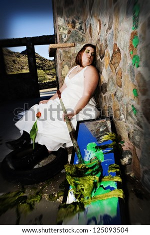 A plus size bride trashes her wedding dress with green paint - stock photo