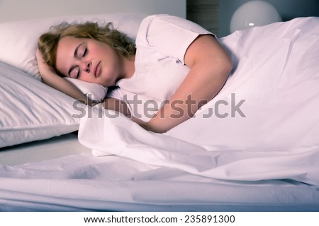 A plus size young woman sleeping in bed at night.  - stock photo