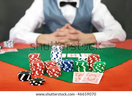 A poker player focusing on his chips and cards, facing the the dealer. Shallow DOF, focus on the front row of chips - stock photo