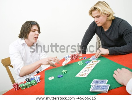 A poker player folding his game by tossing his cards out on the table - stock photo