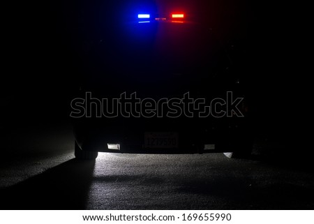 A police car at night with its lights on. *image shot low key on purpose to leave room for copy space.
