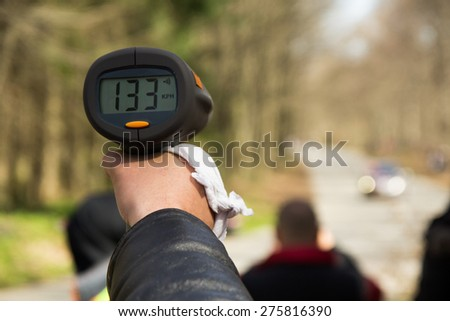 A police man hand pointing radar gun at speeding car.Concept: Crime,Speeding,traffic,surveillance - stock photo