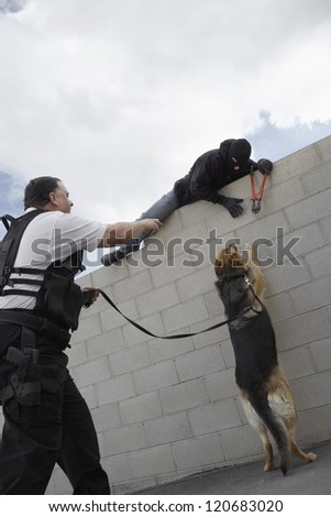 A police man with trained dog catching thief - stock photo