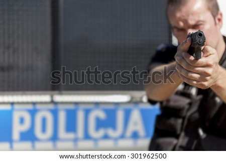 A police officer aiming with gun (focus on gun) - stock photo