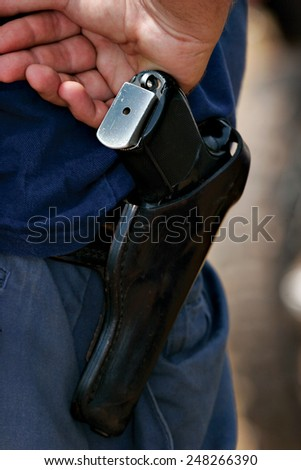 A policeman's gun in its holster on his hip. - stock photo