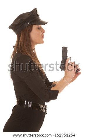A policewoman is holding up a gun blowing on it.
