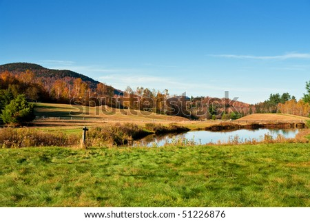 A pond in the country in Autumn in New England in horizontal view - stock photo