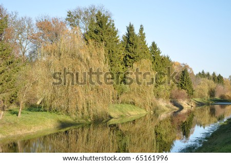 a pond is in an autumn city park - stock photo