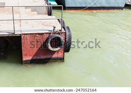 a pontoon with recycled old tyres used as bumpers and muddy water - stock photo