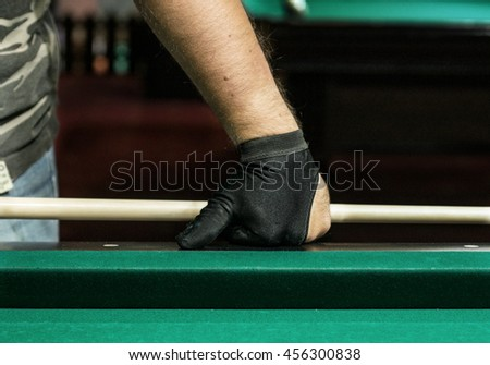 A pool player hand in a glove pressed upon a table
