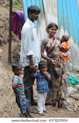 A poor Indian family of father mother and three children standing at the construction site they work at.