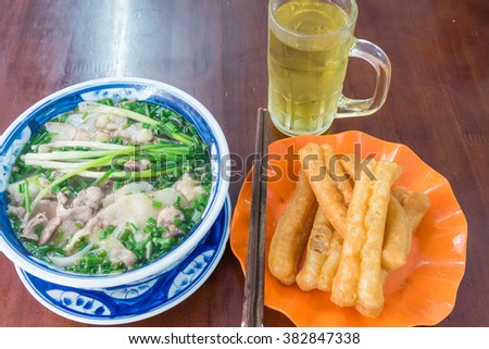 A popular Vietnamese breakfast set with bowl of fresh Vietnamese beef rice noodle soup (Pho Bo) served with sliced rare beef, scallions and few herbs. Side dish is Youtiao (cakwe) and iced tea. - stock photo