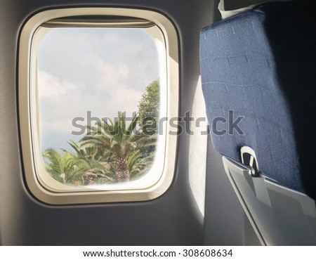 A porthole of airplane with tropical view - stock photo