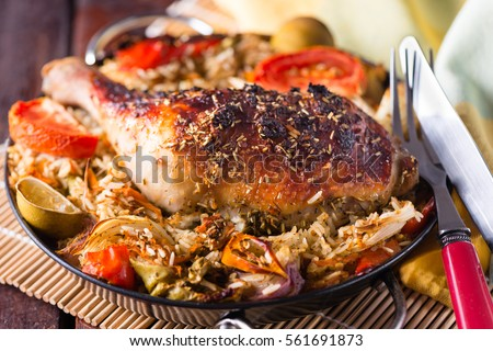 A Portion Baked chicken leg with rice and vegetables in a small black pan