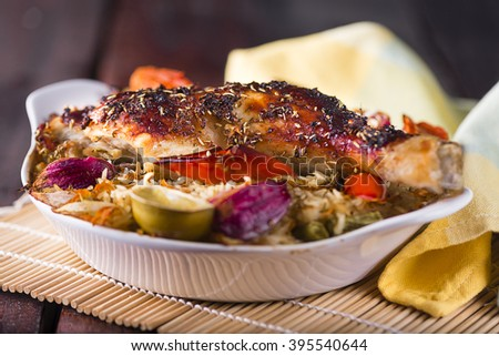 A Portion Baked chicken leg with rice and vegetables in a small white plate