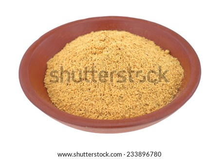 A portion of fajita seasoning mix in a small red bowl on a white background.