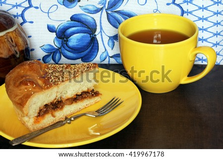 A portion of traditional fresh baked homemade cabbage pie (tart, pasty, cake, calzone, kulebyaka) with sesame on the yellow plate serving with a cup of tea and vintage fork - stock photo