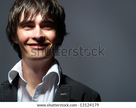 A portrait about a trendy charming young man who is smiling and he has a glamorous look. He is wearing a white shirt and a black suit. - stock photo