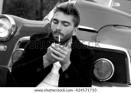 A portrait modern man is near the car. A young man is posing with a cigarette near the vintage car.  He is wearing fashionable  hairdo  and a short beard. Blackly-white shot           - stock photo