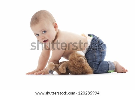 A portrait of a baby boy wearing blue jeans. High key image photographed in the studio. - stock photo