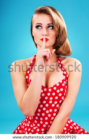 a portrait of a beautiful blonde with a finger on her lips showing to keep silence, hush - stock photo