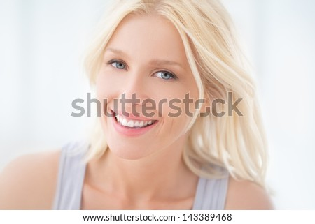 A portrait of a beautiful blonde woman smiling. - stock photo