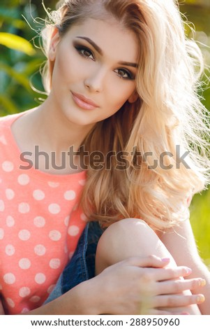 A portrait of a beautiful blonde young Caucasian woman outdoor. Young smiling woman outdoors portrait. Soft sunny colors.Close portrait.  - stock photo