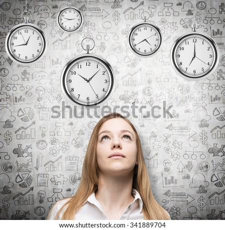 A portrait of a beautiful lady who is looking at the hovering pocket watches. A concept of a value of time in business. Business icons are drawn over the concrete background. - stock photo