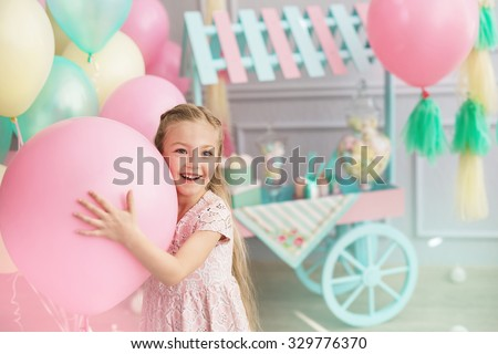 A portrait of a beautiful little girl smiles and holds in a hands a big color balloon in the studio with many balloons and a toy candy shop - stock photo
