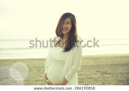 A portrait of a beautiful pregnant woman smile brightly in white dress on the beach - stock photo