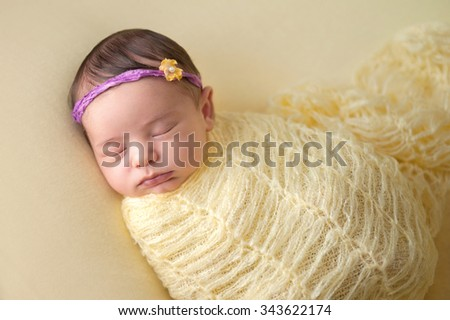 A portrait of a beautiful, sleeping, two week old, newborn baby girl wearing a flower headband. She is swaddled with a knitted mohair wrap. - stock photo