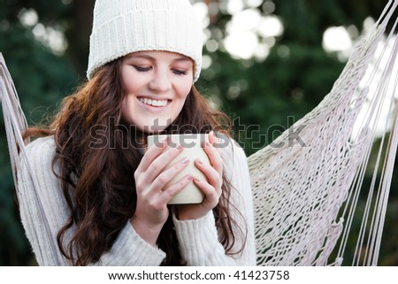 A portrait of a beautiful teenager outdoor drinking coffee