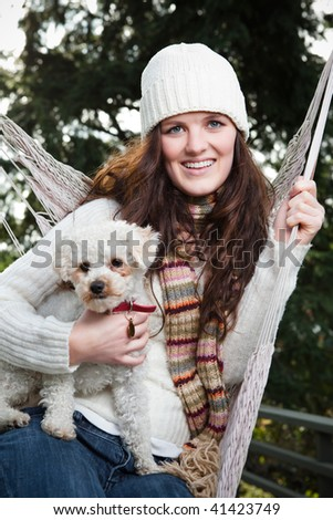 A portrait of a beautiful teenager outdoor relaxing with her dog