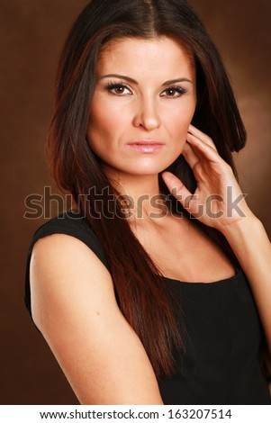 A portrait of a beautiful woman isolated on brown background - stock photo